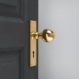Round Door Knobs on Rectangular Backplate Lock Set - Polished Brass